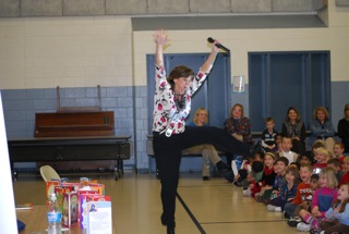 Debbie leaping for joy on a school visit